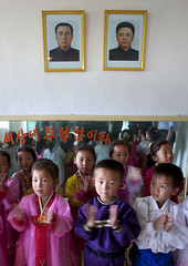North Korean children in a primary school below the portraits of the Dear Leaders, South Pyongan Province, Chongsan-ri Cooperative Farm, North Korea (Eric Lafforgue) Tags: 2718 applause asia asianethnicity boys childhood children chongsanri chosonot clappinghands communism cultofpersonality dictators dictatorship dprk education elementaryschool fatherandson girls groupofpeople humanbeing humanrepresentation ideology indoors innocence kimilsung kimjongil koreanculture learning lookingatcamera northkorea northkorean officialportraits patriotism politicians politicsandgovernment primaryschool propaganda pupils school vertical youth chongsanricooperativefarm southpyonganprovince 北朝鮮 북한 朝鮮民主主義人民共和国 조선 coreadelnorte coréedunord coréiadonorte coreiadonorte 조선민주주의인민공화국 เกาหลีเหนือ קוריאההצפונית koreapółnocna koreautara kuzeykore nordkorea північнакорея севернакореја севернакорея severníkorea βόρειακορέα