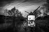 Floodwater, a crane & the photographers bicycle (AlphaAndi) Tags: mono monochrome bike bicycle flood floodwater fullframe vollformat langzeitbelichtung urban wow water wasser dof trier tiefenschärfe sony streets streetshots streetshooting sky himmel crane moselkran