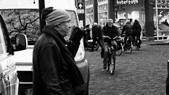 Giant Normal Dwarf (Alfred Grupstra) Tags: people blackandwhite urbanscene citylife street men city outdoors bicycle crowd editorial cycling cultures commuter citystreet phone