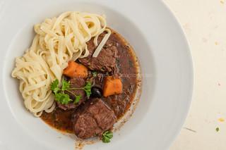 Boeuf en Daube Provenal served with noodles.