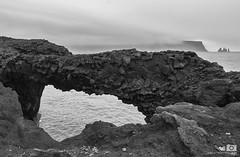 Twisted basalt column natural bridge (petemenzies.com) Tags: basalt column bridge arch rock geology volcanic lava hexagon natural iceland nature vik dyrholaey travel sea sky landscape water ocean coast twisted blackandwhite bnw