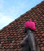 Lady with a pussy hat (Rosmarie Voegtli) Tags: pussyhat statue arlesheim roof tiles pink hat wool demonstrating