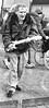 I Wanna Hold Your Hand (tcees) Tags: busker x100 fujifilm finepix bw mono monochrome blackandwhite sidewalk rain wet pavement outdoor urban man streetphotography street daytime umbrella guitar singer glass wheelchair hat