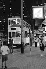 Streetcar Ride through Wan Chai (oxfordblues84) Tags: hongkong peoplesrepublicofchina china oat overseasadventuretravel wanchai 灣仔 tram hongkongtram hongkongstreetcar happyvalleyhongkong happyvalley bw blackandwhite streetscene streetsceneafterdark eveningstreetscene chinese man men pedestrians pedestrian 7eleven sign pole