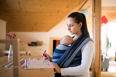 Beautiful mother in kitchen with her son sleeping in sling (antelhawi) Tags: child mother parent adult baby family kid young two people enjoying love cute small holding babycarrier inside sling wrap relationship white striped babywear babywrap babysling son together blue carrying brunette indoors sleeping home woman mom mommy boy sunny sunlight babyboy reading book studying sitting table wooden ponytail beam