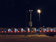 Friday night lights (KevinIrvineChi) Tags: parking lot manhole cover iphone7 iphone light red sky night chicago heavy rail railcars trains kimball brownline cta car cars paved pavement lights
