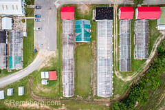 Aerial view looking directly down at several greenhouses and other agriculture buildings on farm, Tifton, Georgia. (Remsberg Photos) Tags: farm georgia tifton uga outdoors aerial agriculture drone glass plantnursery builtstructure botany conservatory highangle building architecture greenhouse agriculturebuildings shed lookingdown usa