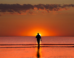 Stranger on the shore (adrians_art) Tags: beach shore coast pettlevel rocks sand pebbles water sea wet tide tidal red yellow gold orange amber sky clouds people silhouettes shadows reflections black white waves eastsussex uk england evening