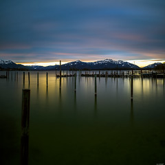 Sea of poles (Rico the noob) Tags: chiemsee d850 landscape nature water germany outdoor lake 2470mmf28 clouds longexposure 2017 reflection wood published sky dof 2470mm sunrise snow mountains