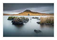Devoke Water (Long Exp1) (Dave Fieldhouse Photography) Tags: still grim moody smooth grey bleak devokewater devoke cumbria lakedistrict lakes lake water nationalpark winter weather longexposure littlestopper leefilters rocks grasses grass boatshouse fell landscape outdoors countryside fuji fujifilm fujixt2 wwwdavefieldhousephotographycom birkerfell