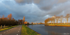 The Last Sunshine of the Day (Johan Konz) Tags: sunset sunshine warm light atmosphere road canal house building tree clouds dark blue sky outdoor landscape ilpendam waterland netherlands nikon d7500 grass water watercourse