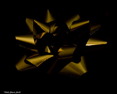 Golden (that_damn_duck) Tags: gold ribbon bow blackbackground