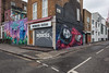 The corner of Buck Street and Stucley Place (Gary Kinsman) Tags: sign signs nw1 london camdentown camden buckstreet camdenhighstreet canoneos5dmarkii canon5dmkii empty quiet topographics newtopographics christmas christmasday desolate advert advertising grey overcast clouds architecture shops shopfront retail independent shutters closed urbanlandscape 2017 canon28mmf18 space noone nemesistattoo tattooparlor stucleyplace backstreet sidestreet graffiti streetart