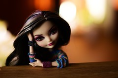 won´t you help me make it through the night (jessandgrace) Tags: doll portrait closeup colorimage colors lights shadow bokeh beads bracelets hands wood table figure sweater face eyes browneyed hair blackhaired pink duchessswan everafterhigh eah pretty beauty glamour cute indoor