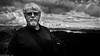 Feeling Dramatic (Neil. Moralee) Tags: neilmoralee newzealand2015neilmoralee man face portrait landscape scene glasses bright dark clouds sky old mature beard moustache shoulder strap lake black white mono bw bandw blackandwhite monochrome dramatic new zealand selfy selfie nikon d7100 stare cold hard neil moralee