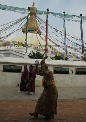 Monk raising his hands over his head to do prostrations, monks circumambulating the great stupa, Boudha, Kathmandu, Nepal