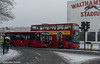 Buses To The Stadium (M C Smith) Tags: bus buses snow snowing red walthamstow dog track housing trafficlights fence barriers railing tree branches slush pavement kerb sky grey yellow tracks poster advertising letters symbols numbers flowers baskets triangle