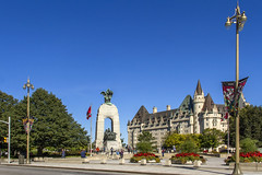 Ottawa's Confederation Square (Kev Gregory (General)) Tags: national square ottawa capital city ontario canada red white flag building gothic grand park flowers trees colour colourful arch road lamp lampposts blue clear sky summer warm tourists tourism verdigris roof bushes idyllic beautiful concrete pavement quite rest architecture clean impressive proud heritage tidy safe providing confederation war château fairmont memorial laurier backdrop canon 7d kev gregory