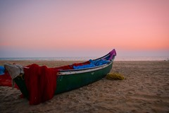A Boat resting on the beach (breathacker2010) Tags: india kerala sand beach landscape boat sunset colors orangesky sea arabian arabiansea water bekal travel