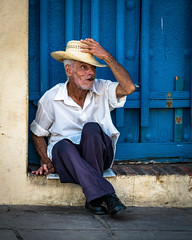 Tip of the Hat (Wits End Photography) Tags: instagram opening sidewalk pavement color roadway portal street people structure route doorway multicolored entrance cigar door building hat blue colorful road travelphotography drive objects colors architecture entry cuba streetphotography places trinidad