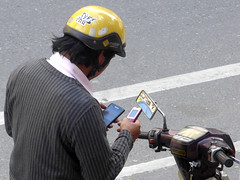 A phone for all occasions (Roving I) Tags: helmets motorcycles cellphones samsung street twophones technology danang vietnam