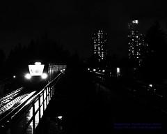 Night Lights With Incoming #Skytrain Mark III & Distant #Burnaby Condo Towers (AvgeekJoe) Tags: artmarkiii bw blackwhite blackandwhite bombardier bombardierartmarkiii bombardierinnoviametro bombardierinnoviametro300 britishcolumbia canada d5300 dslr importedkeywordtags innoviametro innoviametro300 lightrail nikon nikond5300 sigma1835mmf18 sigma1835mmf18dchsmart sigma1835mmf18dchsmartfornikon sigmaartlens skytrain train translink vancouver masstransit night nightphoto nightphotograph nightphotography nightshot rail supertrain transit urbanrail