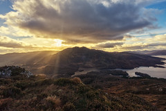 Ben Venue from Ben A'an (MilesGrayPhotography (AnimalsBeforeHumans)) Tags: 1635 fe1635mm sonyfe1635mmf4zaoss autumn a7ii britain benaan benvenue dusk europe evening fe f4 glow golden goldenhour haze iconic ilce7m2 landscape lens loch landscapephotography lochlomond lochlomondandthetrossachs trossachs lochkatrine hill mountains outdoors oss clouds photography tranquil reflections rocks rays raysoflight scotland sky scenic skyline sunset sunlight sunshine sonya7ii sony sunburst sunflare scottish scottishlandscapephotography scottishhighlands twilight trees uk unitedkingdom volcanic valley wide wideangle zeiss