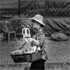 Thai street vendor (John Riper) Tags: johnriper street photography straatfotografie square vierkant bw black white zwartwit mono monochrome bangkok thailand candid john riper xt2 fujifilm vendor hat hawker money banknotes umbrella chairs woman