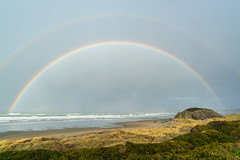 rainbow (Earl Robicheaux Photography, LLC) Tags: environment scenery water ocean sky nature land coast coastline seaside shore beach rocks timeofday color style format alignment horizontal panorama panoramic timeexposure longexposure scenic rock boulder naturalobject outcropping rockoutcrop rockformation wave breaker breakers roller surf swell whitecap worldregions countries northamerica unitedstatesofamerica oregon bandon oregoncoast seasons summer summertime evening closeofday sunset late seashore sanddunes sand weather rainbow arc curve bandofcolors halfmoon or usa