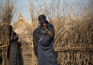 Oromo veiled woman with a burqa standing in front of her village, Amhara region, Artuma, Ethiopia