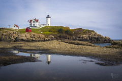 Nubblepuddle (RobertCross1 (off and on)) Tags: 20mmf17panasonic atlantic capeneddick em5 me maine newengland nubble omd olympus usa york architecture beach building clouds coast flag landscape lighthouse ocean puddle reflection rocks seascape tidepool water