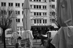 Am Schloßhof (01) (Rüdiger Stehn) Tags: bauwerk sonnenschirm fassade profanbau architektur 2000er 2000s europa mitteleuropa deutschland norddeutschland schleswigholstein gebäude canoneos550d kiel rüdigerstehn 2018 neubau schwarzweis blackandwhite menschen leute
