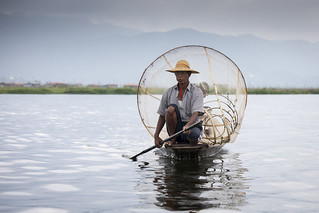 Inle Lake fisherman with cone shaped net on a boat, Myanmar