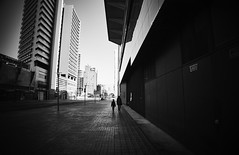 Alone in the city... (elgunto) Tags: barcelona poblenou diagonalmar wideangle zoomlens monochrome blackwhite silhouettes street people sonya7 konicaminolta minoltaaf1735mmf284 perspective architecture buildings laea4