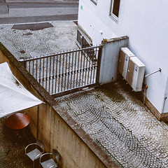 Modern Concrete Beauty (Thomas Listl) Tags: thomaslistl color concrete chairs table cobblestones fence diagonal lines street urban birdseyeview building vsco 35mm square