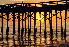 Sunset Pier (Karen_Chappell) Tags: pier wharf dock sunset orange black beach ocean pacific california balboabeach balboa orangecounty sun evening silhouette people ripples reflections usa travel