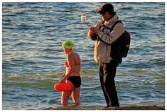 Taking the Wrong Picture (HereInVancouver) Tags: woman bikini swimming ocean canada february cold selfie candid streetphotography framed vancouverswestend englishbay thingstodobythewater canong3x hat backpack wintercoat beach pacific vancouver bc