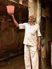 Rain Man (solas53) Tags: rain man person bucket wet stand india smile colour color monsoon