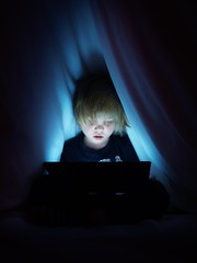 Electronic Zombie (RyanMussbacher) Tags: screentime dark blue blankets hiding child computers