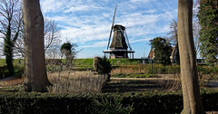 Framed By Trees (Alfred Grupstra) Tags: windmill old history ruralscene nature architecture cultures woodmaterial sky grass landscape europe famousplace tree outdoors netherlands blue summer oldfashioned scenics clouds dike