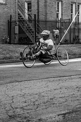 Wheelchair Athlete (burnt dirt) Tags: wheelchair bicycle bike athlete competition helmet uniform marathon halfmarathon 5k course race racer pedal wheel flag road street amputee prosthetic sunglasses glasses downtown town city bw blackandwhite fujifilm camera metro station busstation trainstation hero military xt1 streetphotography urban candid portrait documentary laugh smile winner medal sport vehicle outdoor people person abb5k houston texas houstonmarathon houstonhalfmarathon chevron man woman crank gloves sunny cold topend
