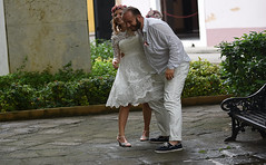 About to Lift His Bride (Poocher7) Tags: people portrait couple wedding bride groom candid streetphotography courtyard havana cuba carribean smiles laughter happy pinkshoes weddingdress hairwreath pinkflowers whiteshirt whitepants love romantic bench cobblestones beard photoshoot boda