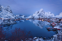 Winter in Reine (inkasinclair) Tags: reine winter snow mountains olstinden gravdalsbukta reflection water houses rorbuer red trees norway lofoten islands december lights