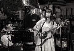 Voice of an Angel (Anne Worner) Tags: anneworner blackandwhite em5 georgetown interior bw display earrings glasses guitar guitarshop guitarist longhair mike monochrome musicstand olympus playing storeinterior strings sweatshirts woman microphone musician stringedinstrument instrument notestand street candid streetphotography clotheshanger