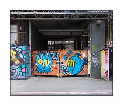 Street Art (Dscreet & Nylon), East London, England. (Joseph O'Malley64) Tags: dscreet dbltrbl vinnienylon nylon graffiti urbanart publicart freeart streetart eastlondon eastend london england uk britain british greatbritain art artists artistry artworks murals muralists defaced defacement gates plywoodpanels woodenpanels wheels buildingsite constructionsite scaffold scaffolding brickwork bricksmortar cement pointing reinforcedsteeljoists steelbeams entrance exit ramp hordings signs signage healthsafety sitesafety accesscovers tarmac granitekerbing redroute nostoppingatanytime parkingrestrictions characters signaturecharacters urban urbanlandscape chain bolt aerosol cans spray paint fujix x100t accuracyprecision