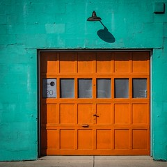 That Building (tim.perdue) Tags: that building short north arts district columbus ohio garage door window wall concrete colorful multicolored teal orange block light shadow orbit design colors poplar avenue iphone instagram mobile olympus omd em10mkii blue turquoise