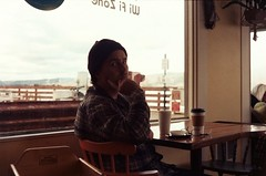 Morning Coffee with Joel (Anne Abscission) Tags: elixircoffee southbend washington pnw morningcoffee traveling roadtrip waterfront pacificnorthwest availablelight coffee indoor january winter olympustrip olympustrip35 analog 35mmfilm ferraniasolaris ferrania expiredfilm ishootfilm staybrokeshootfilm film backlit joel coffeeshop willapaharbor elixirteaandespresso cafe