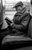 2018_024 (Chilanga Cement) Tags: fuji fujix100t fujix100f x100t xseries x100f x100s x100 bw blackandwhite monochrome candid man reading train commuter commute book agathachristie cap hat