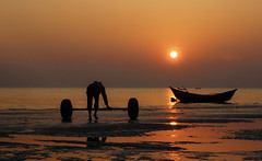The sky broke like an egg into full sunset and the water caught fire (Hafizul Haider Robin) Tags: sunset sun orange sky sea boat bangladesh kuakata travel worker last light