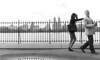 Exit Stage Left (Greg Adams Photography) Tags: nyc newyorkcity newyork centralpark people strangers skyline monochrome bw blackandwhite man woman couple fence moving hhsc2000 travels resevoir water playfull